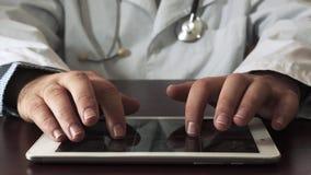 Αρσενικό γιατρών που χρησιμοποιεί την ψηφιακή ταμπλέτα κλείστε επάνω απόθεμα βίντεο