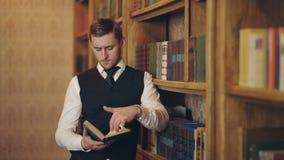 Αρσενικό διαβασμένο δημοσιογράφος βιβλίο που κάνει την έρευνα για τη στάση άρθρου κοντά στα ράφια Έξυπνο βιβλίο και ανάλυση εκμετ φιλμ μικρού μήκους