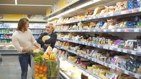 Αρσενικό και θηλυκό κάρρο ώθησης αγοραστών με τα προϊόντα παντοπωλείων στο διάδρομο υπεραγορών φιλμ μικρού μήκους