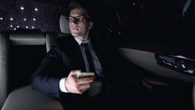 Αρσενικό κοστουμιών με τη φίλη στη πίσω θέση του αυτοκινήτου ως οδήγηση του σπιτιού, φλερτ φιλμ μικρού μήκους