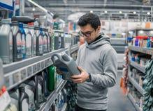 Αρσενικό λαδώνοντας πετρέλαιο μηχανών αγοράς πελατών στην υπεραγορά αυτοκινήτων Στοκ Εικόνα