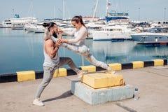 Αρσενικό λεωφορείο που βοηθά τη νέα άσκηση γυναικών στην αποβάθρα στοκ φωτογραφία με δικαίωμα ελεύθερης χρήσης
