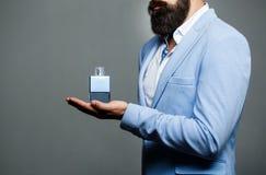 Αρσενικό να κρατήσει ψηλά μπουκάλι του αρώματος Άρωμα ατόμων, άρωμα Μπουκάλι αρώματος ή της Κολωνίας και αρωματοποιία, καλλυντικά στοκ φωτογραφία με δικαίωμα ελεύθερης χρήσης