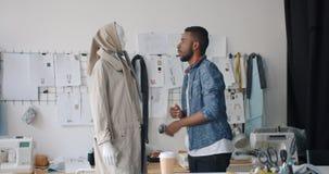 Αρσενικό ντύνοντας μανεκέν σχεδιαστών που κοιτάζει και που χαμογελά απολαμβάνοντας το μοντέρνο ένδυμα απόθεμα βίντεο