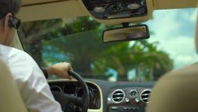 Αρσενικό οδηγώντας αυτοκίνητο πολυτέλειας στη παραθεριστική πόλη, προσωπικός οδηγός, ιδιωτικό αυτοκίνητο απόθεμα βίντεο