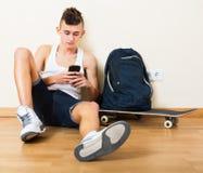 Αρσενικό παιχνίδι εφήβων με το τηλέφωνο Στοκ Φωτογραφίες