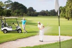 Αρσενικό παιχνίδι παικτών γκολφ στην παγίδα άμμου από τη γυναίκα Στοκ Εικόνες