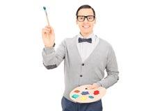 Αρσενικό πινέλο εκμετάλλευσης καλλιτεχνών και μια παλέτα χρώματος Στοκ φωτογραφίες με δικαίωμα ελεύθερης χρήσης