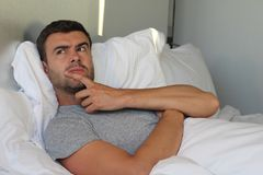 Αρσενικό πονηριών που σχεδιάζει μια εκδίκηση στο κρεβάτι στοκ εικόνες με δικαίωμα ελεύθερης χρήσης