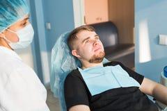 αρσενικό πορτρέτο Οδοντική έννοια προσοχής Η οδοντική επιθεώρηση δίνεται στο όμορφο άτομο που περιβάλλεται από τον οδοντίατρο Στοκ φωτογραφία με δικαίωμα ελεύθερης χρήσης