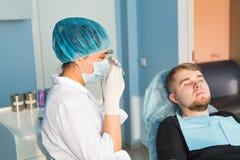 αρσενικό πορτρέτο Οδοντική έννοια προσοχής Η οδοντική επιθεώρηση δίνεται στο όμορφο άτομο που περιβάλλεται από τον οδοντίατρο Στοκ εικόνες με δικαίωμα ελεύθερης χρήσης