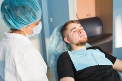αρσενικό πορτρέτο Οδοντική έννοια προσοχής Η οδοντική επιθεώρηση δίνεται στο όμορφο άτομο που περιβάλλεται από τον οδοντίατρο Στοκ εικόνα με δικαίωμα ελεύθερης χρήσης