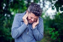 Αρσενικό που έχει τον πόνο αυτιών σχετικά με επίπονο επικεφαλής υπαίθριό του στοκ φωτογραφία με δικαίωμα ελεύθερης χρήσης