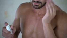 Αρσενικό που εφαρμόζει το λοσιόν στη γενειάδα για να υποκινήσει την αύξηση της του προσώπου τρίχας, καλλυντικά απόθεμα βίντεο