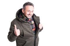 Αρσενικό που θέτει φορώντας το χειμερινό σακάκι που παρουσιάζει όπως τη χειρονομία Στοκ Εικόνες