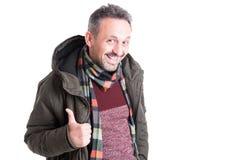 Αρσενικό που θέτει φορώντας το χειμερινό σακάκι που παρουσιάζει αντίχειρα επάνω στη χειρονομία Στοκ Εικόνες
