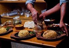 Αρσενικό που προετοιμάζει τα ασιατικά γεύματα με το ρύζι σε μια κουζίνα στοκ εικόνες με δικαίωμα ελεύθερης χρήσης