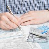 Αρσενικό που συμπληρώνει τη φορολογική μορφή 1040 ΗΠΑ - μια προς ένα αναλογία Στοκ εικόνες με δικαίωμα ελεύθερης χρήσης