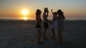 Αρσενικό που χορεύει με τρεις θηλυκούς φίλους σε μια παραλία στο ηλιοβασίλεμα απόθεμα βίντεο