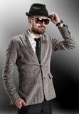 Αρσενικό πρότυπο γυαλιά ηλίου στα γκρίζα σακακιών καπέλων Στοκ Εικόνα