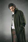 Αρσενικό πρότυπο μόδας στο πράσινο σκηνικό παλτών και σύστασης στοκ εικόνα με δικαίωμα ελεύθερης χρήσης