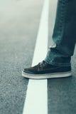 Αρσενικό πόδι που στέκεται στην άσπρη γραμμή Πέρασμα της έννοιας γραμμών Στοκ Εικόνα
