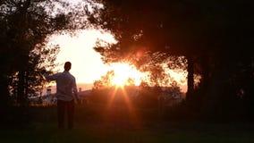 Αρσενικό στην ημι σκιαγραφία που χαιρετίζει την πρόκληση της επιτυχίας σε μια αστική σκηνή φιλμ μικρού μήκους