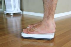 Αρσενικό στην κλίμακα βάρους για το βάρος ελέγχου, έννοια διατροφής στοκ εικόνες