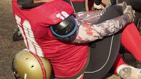 Αρσενικό στην ομοιόμορφη χαλάρωση στην πίσσα, φορείς αμερικανικού ποδοσφαίρου που κάθεται στο έδαφος απόθεμα βίντεο