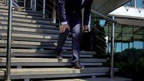 Αρσενικό στο κοστούμι σχετικά με το γόνατο, που πηγαίνει κάτω, κοινή ζημία, στατικός τρόπος ζωής στοκ εικόνα