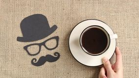 Αρσενικό σχέδιο σκιαγραφιών με το mustache, τα γυαλιά και το καπέλο με το φλιτζάνι του καφέ στο burlap υπόβαθρο
