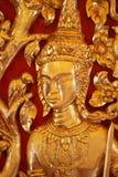 Αρσενικό ταϊλανδικό άγαλμα αγγέλου κινηματογραφήσεων σε πρώτο πλάνο που γεμίζουν με το χρυσό φύλλο με τα κόκκινα υπόβαθρα, ξύλινο Στοκ Εικόνες
