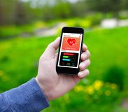 Αρσενικό τηλέφωνο εκμετάλλευσης χεριών με app την ακολουθώντας οθόνη δραστηριότητας υγείας Στοκ Εικόνες
