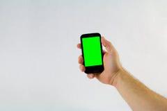 Αρσενικό τηλέφωνο κυττάρων εκμετάλλευσης χεριών στο άσπρο υπόβαθρο με το πράσινο scre Στοκ Εικόνες