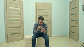 Αρσενικό υπομονετικό χρησιμοποιώντας τηλέφωνο περιμένοντας το διορισμό γιατρών του απόθεμα βίντεο