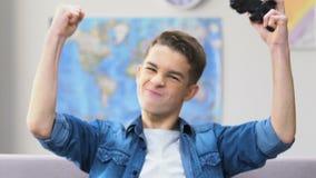 Αρσενικό υψηλό schooler που κερδίζει το τηλεοπτικό παιχνίδι, καναπές που χαλαρώνει, ανταγωνιστικό τυχερό παιχνίδι απόθεμα βίντεο