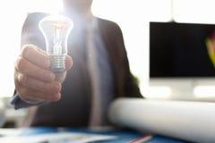 Αρσενικό χέρι με φωτισμένος lightbulb διανυσματική απεικόνιση