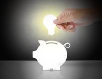 Αρσενικό χέρι που βάζει τη λάμπα φωτός σε μια piggy τράπεζα Στοκ εικόνα με δικαίωμα ελεύθερης χρήσης