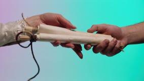 Αρσενικό χέρι που δίνει ένα αρχαίο, κυλημένο χειρόγραφο σε ένα χέρι γυναικών, που απομονώνεται στο πράσινο και ρόδινο υπόβαθρο απ απόθεμα βίντεο