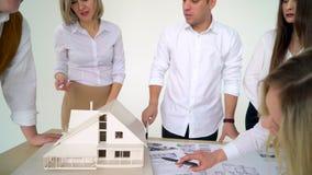 Αρσενικό χέρι που δείχνει στη μικρογραφία σπιτιών κύριων πορτών με ένα μολύβι στον υπολογιστή γραφείου γραφείων του κλείστε επάνω φιλμ μικρού μήκους