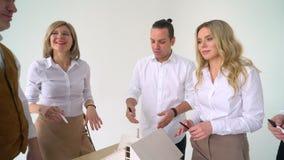 Αρσενικό χέρι που δείχνει στη μικρογραφία σπιτιών κύριων πορτών με ένα μολύβι στον υπολογιστή γραφείου γραφείων του κλείστε επάνω απόθεμα βίντεο