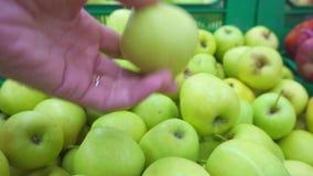 Αρσενικό χέρι που επιλέγει τα φρέσκα μήλα στην υπεραγορά απόθεμα βίντεο