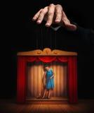 Αρσενικό χέρι που ελέγχει μια μικρή μαριονέτα γυναικών Στοκ Φωτογραφία