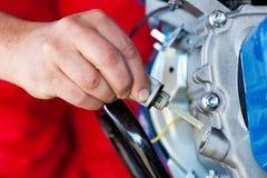 Αρσενικό χέρι που ελέγχει το επίπεδο πετρελαίου Στοκ Φωτογραφίες