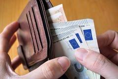 Αρσενικό χέρι που κρατά ένα πορτοφόλι δέρματος και που αποσύρει το ευρωπαϊκό νόμισμα (ευρώ, ΕΥΡ) Στοκ εικόνα με δικαίωμα ελεύθερης χρήσης