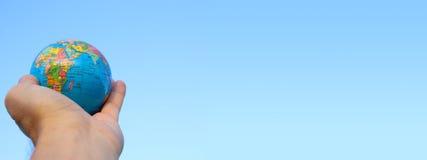 αρσενικό χέρι που κρατά τη μικρή σφαίρα μπροστά από το μπλε ουρανό Στοκ Εικόνες