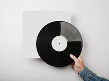 Αρσενικό χέρι που κρατά το βινυλίου πρότυπο λευκωμάτων μουσικής επάνω Στοκ Φωτογραφίες