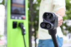 Αρσενικό χέρι που κρατά το μαύρο καλώδιο αυτοκινήτων χρέωσης αυτοκινήτων στοκ φωτογραφίες με δικαίωμα ελεύθερης χρήσης