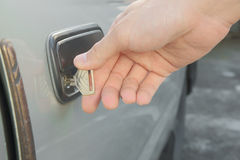 Αρσενικό χέρι που ξεκλειδώνει την παλαιά χρησιμοποιημένη πόρτα αυτοκινήτων Στοκ Εικόνες