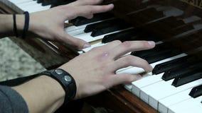 Αρσενικό χέρι που παίζει το πιάνο Ο τύπος παίζει το πιάνο Τα χέρια ενός νεαρού άνδρα πιέζουν τα άσπρα και μαύρα πλήκτρα ενός μουσ φιλμ μικρού μήκους
